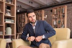 Homem considerável novo que abotoa o café do terno dentro Imagem de Stock