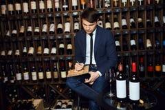 Homem considerável novo que controla o inventário da adega de vinho fotos de stock royalty free