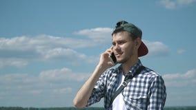 Homem considerável novo que fala no telefone video estoque
