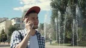 Homem considerável novo que fala no telefone vídeos de arquivo
