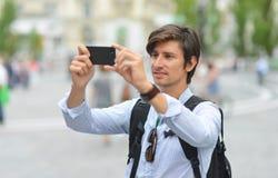 Homem considerável novo que fotografa com o telefone esperto móvel Fotografia de Stock Royalty Free