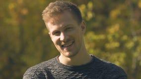 Homem considerável novo que levanta para a câmera na vida do parque do outono, a feliz e a saudável video estoque