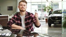 Homem considerável novo que mostra chaves do carro a seu automóvel novo no salão de beleza do negócio video estoque