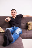 Homem considerável novo que olha a tevê em um sofá em casa foto de stock