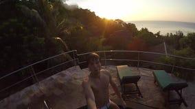 Homem considerável novo que salta na piscina durante o por do sol de surpresa Movimento lento 120fps 1920x1080 filme