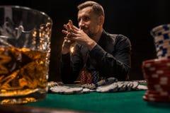 Homem considerável novo que senta-se atrás da tabela do pôquer com cartões e microplaquetas Fotos de Stock Royalty Free