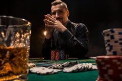 Homem considerável novo que senta-se atrás da tabela do pôquer com cartões e microplaquetas Foto de Stock