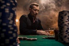 Homem considerável novo que senta-se atrás da tabela do pôquer com cartões e microplaquetas Imagem de Stock Royalty Free