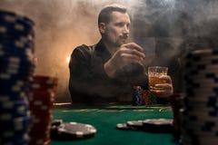 Homem considerável novo que senta-se atrás da tabela do pôquer com cartões e microplaquetas Imagens de Stock