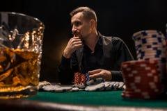 Homem considerável novo que senta-se atrás da tabela do pôquer com cartões e microplaquetas Fotografia de Stock