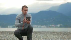 Homem considerável novo que senta-se na praia rochosa Verifica mensagens na tabuleta Atrás do Oceano Pacífico e filme