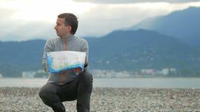 Homem considerável novo que senta-se na praia rochosa Verifica o sentido em um mapa de papel Atrás do Oceano Pacífico e filme
