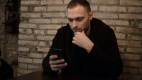 Homem considerável novo que senta-se no café com parede de tijolo e que usa o smartphone, consultando o Internet apenas filme