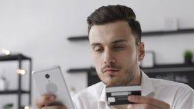 Homem considerável novo que usa o telefone esperto para o pagamento da compra em linha video estoque