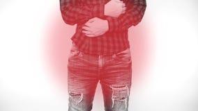 Homem considerável novo sobre o fundo isolado com mão no estômago porque náusea, sentimento doloroso da doença indisposto ache filme
