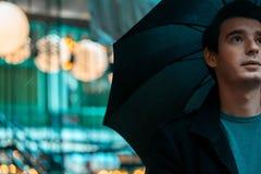 Homem considerável pensativo novo com o guarda-chuva no dia chuvoso que anda no parque fotografia de stock royalty free