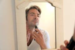 Homem considerável que barbeia na frente do espelho foto de stock