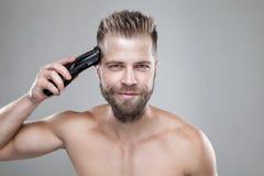 Homem considerável que corta seu próprio cabelo com uma tosquiadeira fotos de stock