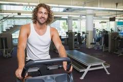 Homem considerável que dá certo na bicicleta de exercício no gym imagens de stock royalty free