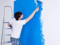 Homem considerável que escova a parede fotos de stock