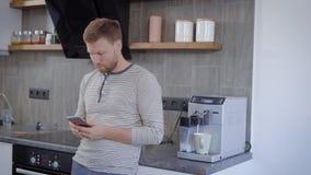 Homem considerável que espera seu café na cozinha home video estoque
