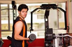 Homem considerável que faz o bíceps que levanta com peso no banco em um gym Fotografia de Stock
