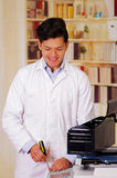 Homem considerável que fixa uma fotocopiadora durante a manutenção usando uma chave de fenda Foto de Stock Royalty Free