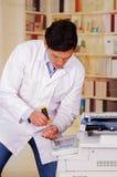 Homem considerável que fixa uma fotocopiadora durante a manutenção usando uma chave de fenda Fotos de Stock