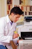 Homem considerável que fixa uma fotocopiadora durante a manutenção usando uma chave de fenda Fotografia de Stock