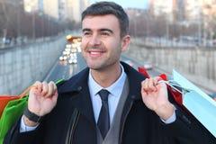 Homem considerável que guarda sacos de compras Fotografia de Stock Royalty Free