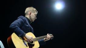 Homem considerável que joga a guitarra acústica na fase no projetor, desempenho desconectado vídeos de arquivo