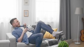 Homem considerável que joga uma guitarra invisível com um telecontrole da tevê em sua mão