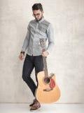 Homem considerável que mantém uma guitarra acústica contra a parede do grunge imagem de stock royalty free