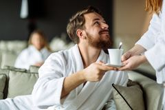 Homem considerável que recebe seu copo do chá imagem de stock