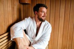 Homem considerável que relaxa na sauna imagem de stock