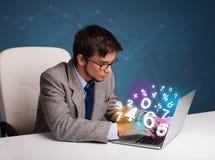 Homem considerável que senta-se na mesa e que datilografa no portátil com número 3d Fotografia de Stock Royalty Free