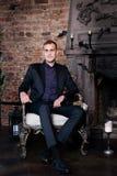 Homem considerável que senta-se no terno no interior luxuoso com chaminé indoor Foto de Stock