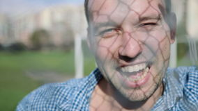Homem considerável que sorri contra uma parede moderna da cerca, exterior vídeos de arquivo