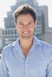 Homem considerável que sorri na câmera em seu balcão imagens de stock royalty free
