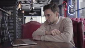 Homem considerável que trabalha com o portátil no fim moderno do café acima Homem de negócios seguro à moda que pensa sobre a res filme