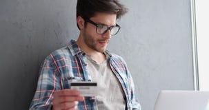Homem considerável que usa o portátil e o cartão de crédito para o pagamento em linha filme