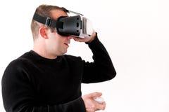 Homem considerável que veste e que joga a realidade virtual no fundo branco isolado Ação do menino no capacete da realidade virtu Fotos de Stock