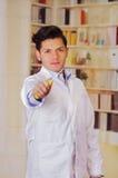 Homem considerável que veste um revestimento branco e que guarda uma chave de fenda Fotografia de Stock