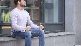 Homem considerável sério ansioso que senta-se fora do escritório video estoque