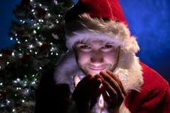 Homem considerável Santa que sorri e que guarda luzes em suas mãos e que olha a câmera com a árvore de Natal no fundo foto de stock