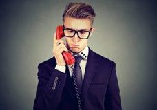 Homem considerável triste que tem a conversação telefônica desagradável que olha para baixo imagem de stock royalty free