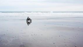 Homem consider?vel novo do moderno que monta o piloto feito sob encomenda moderno da motocicleta na praia preta da areia perto da video estoque