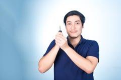 Homem considerável asiático com as chaves de seu carro novo, no backgro azul Fotografia de Stock