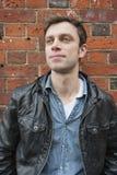 Homem considerável em um casaco de cabedal que olha afastado Fotografia de Stock