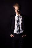 Homem considerável novo em um terno de negócio e em uma camisa branca e laço no estilo formal no estúdio em um fundo preto Fotografia de Stock Royalty Free